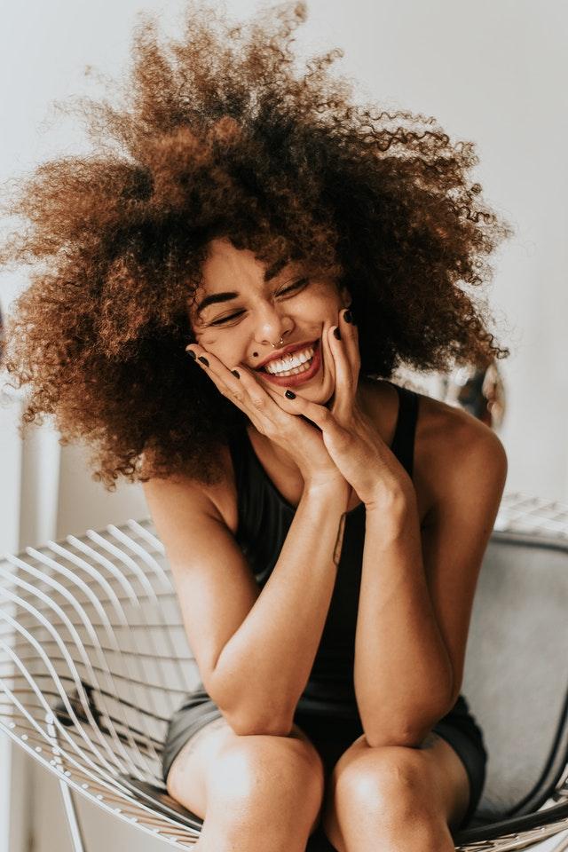 usmívající se brunetka s černě nalakovanými nehty